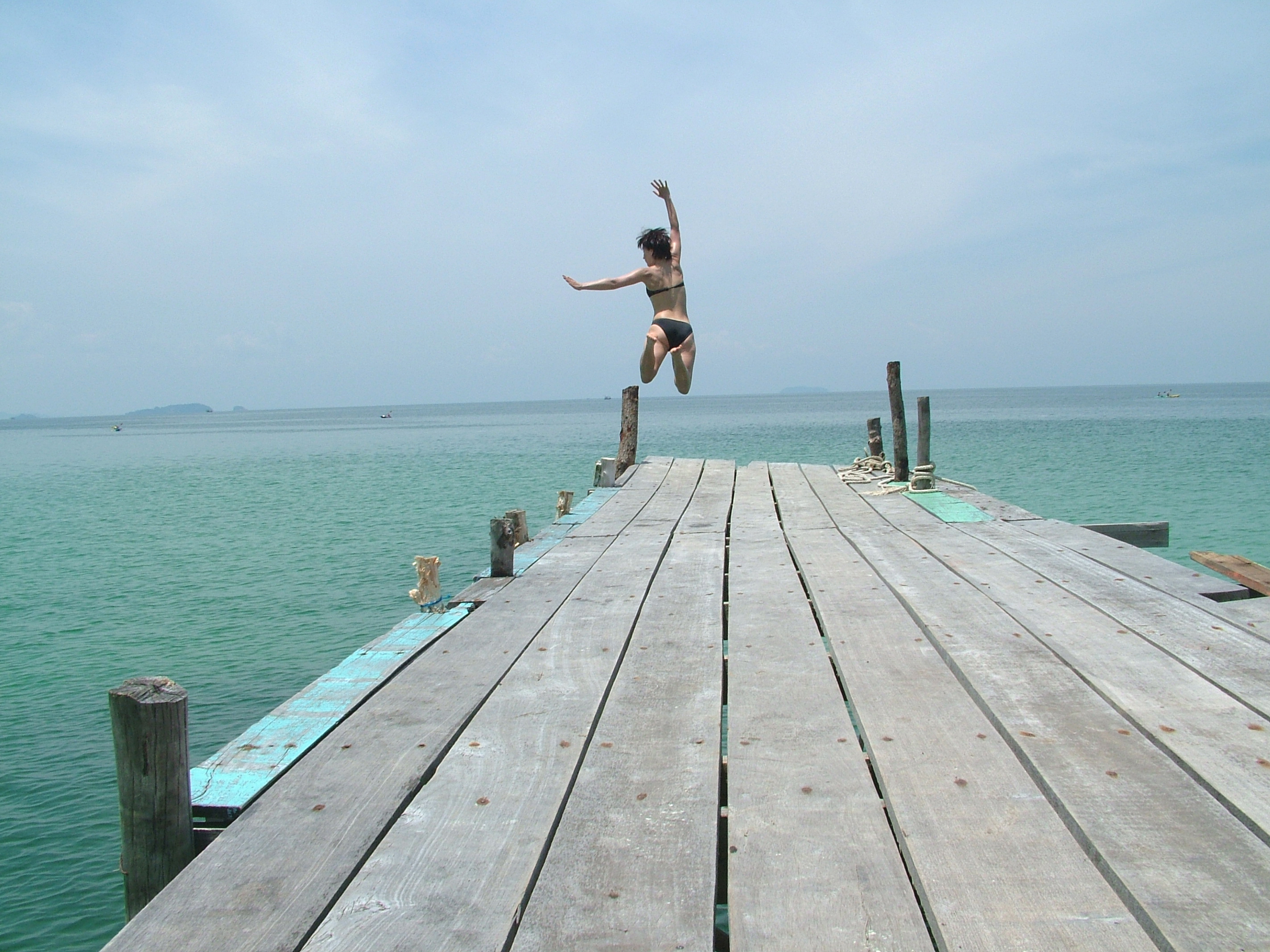 A girl jumping off a pier into the sea