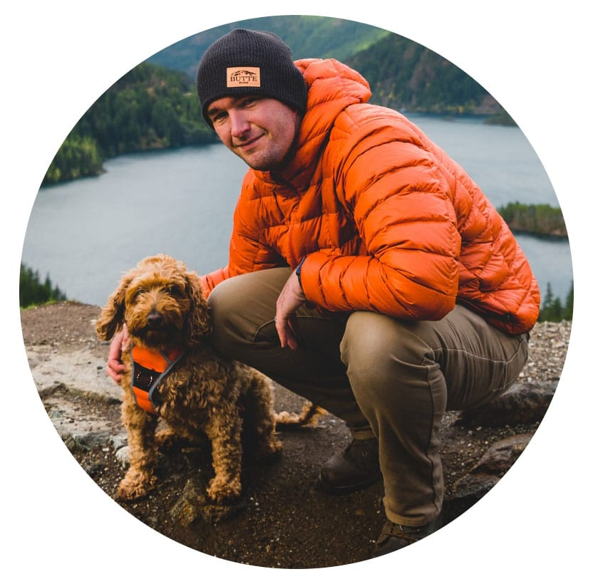 image of a man and dog in outdoor wear near a lake